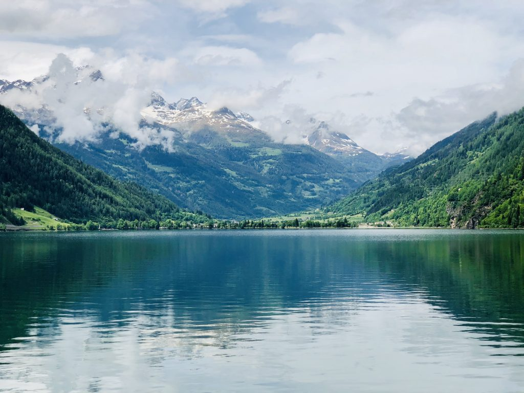 a photo of a lake with a snow capped mountain behind it