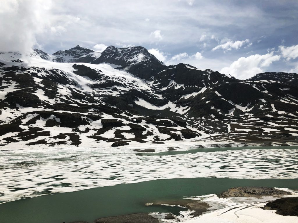 photo of a frozen lake and snow covered mountains