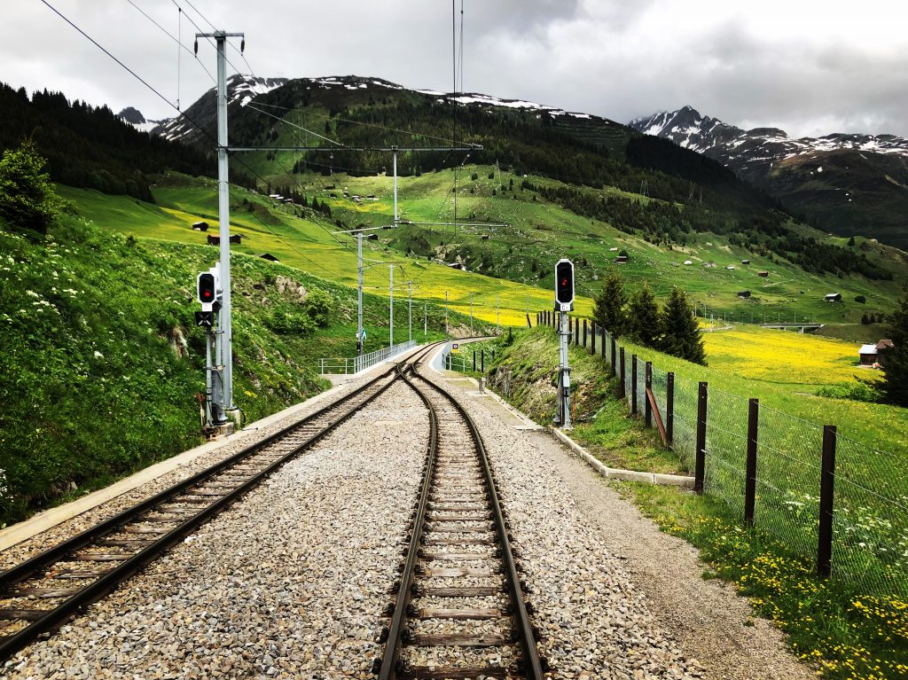 photo of a railroad track in switzerland with mountains in the background and yellow flowers on the green grass