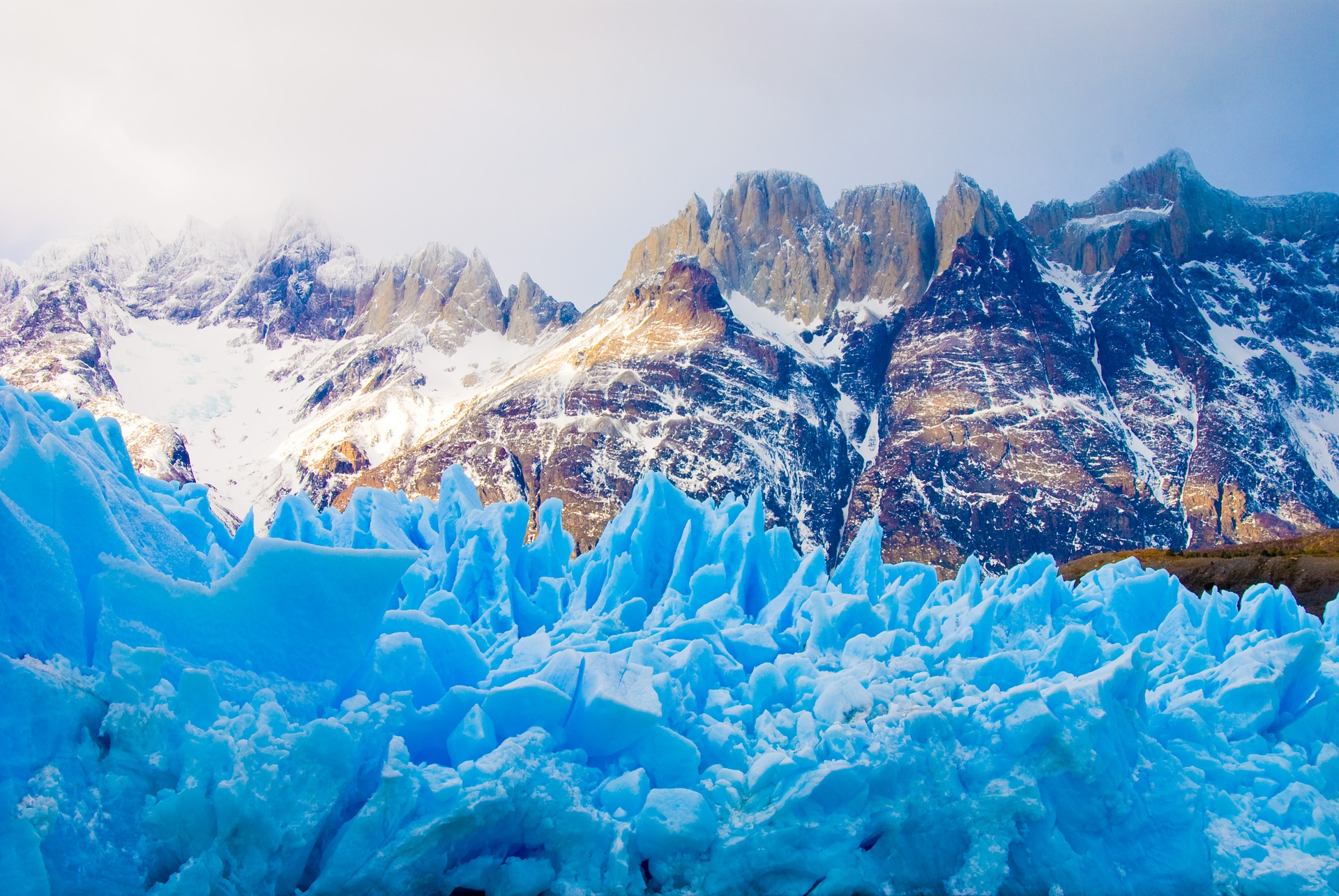 a photo of a glacier in chile and snow covered mountains