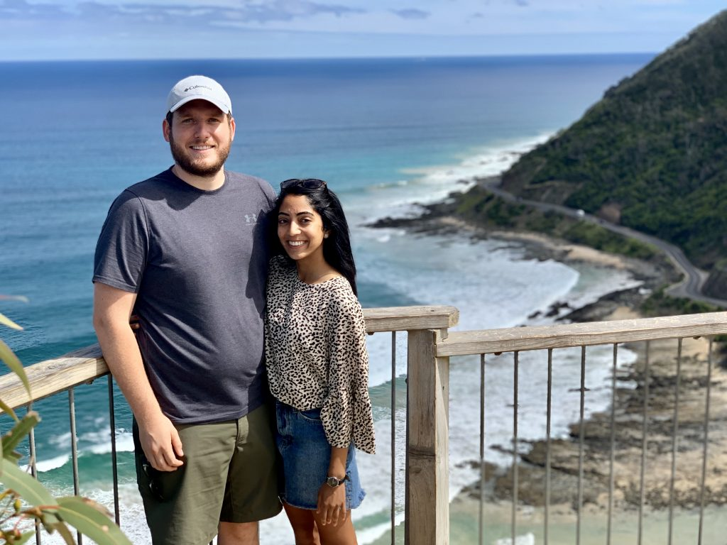 a picture of me and my husband overlooking the ocean while standing on a cliff in australia