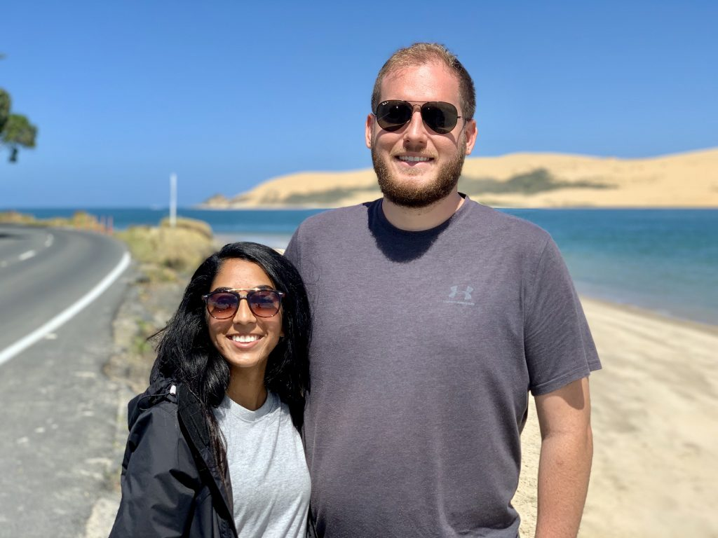 a photo of me and my husband on the beach in new zealand