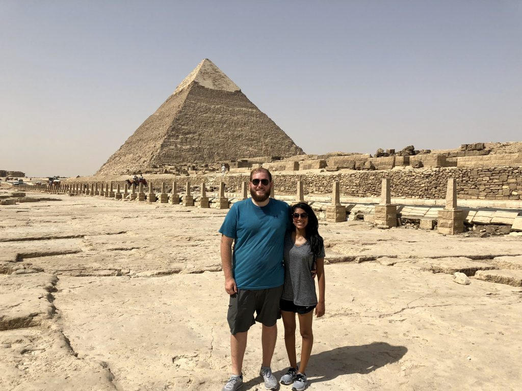 a picture of me and my husband in front of the pyramids in egypt