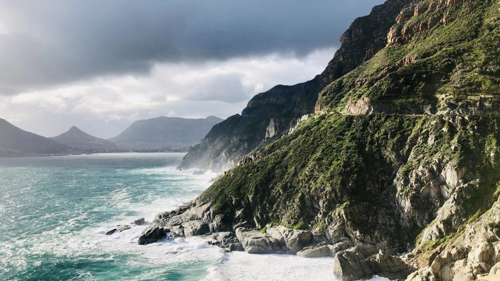 a photo of the ocean hugging a mountain at chapman's peak drive