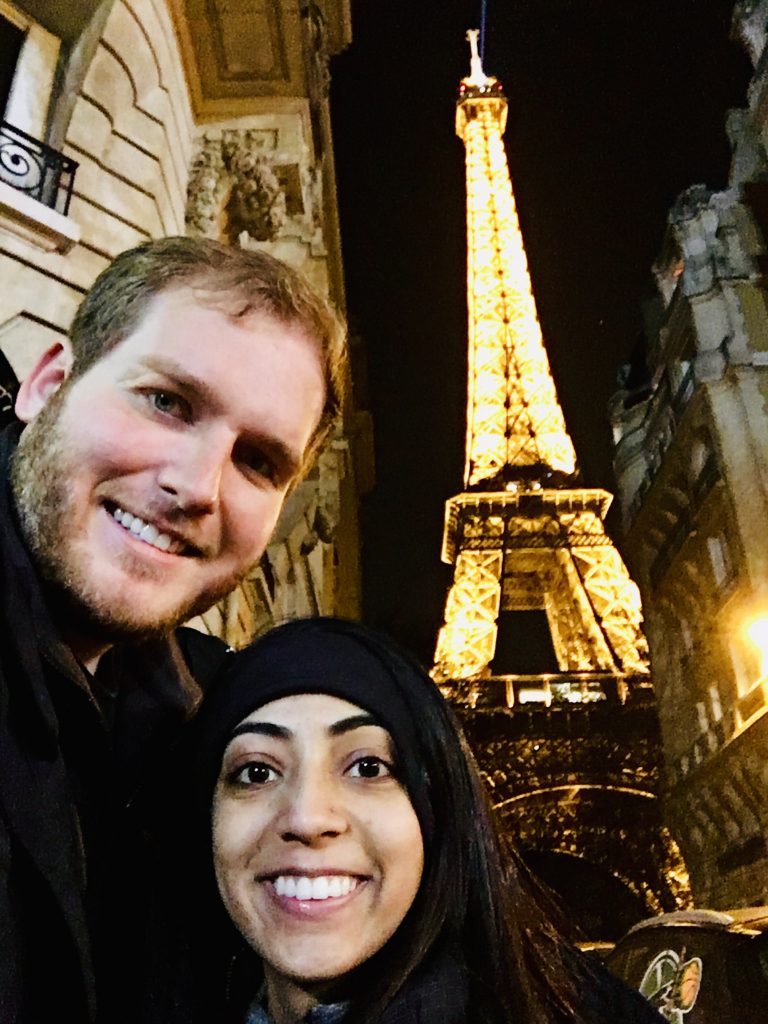 a photo of me and amos standing in front of the eiffel tower in paris at night