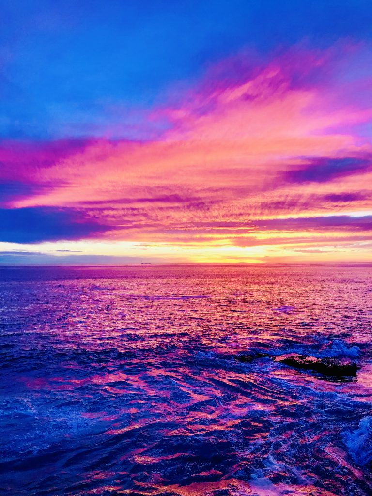 a photo of the sunset in cape town. the sky is bright with shades of blue, purple and pink.