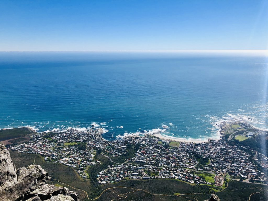 the view from the top of table mountain in cape town. the photo shows the coastline below with the city below as well.