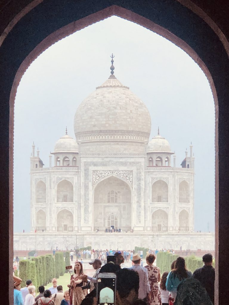 A photo of the Taj Mahal with crowds of people around.